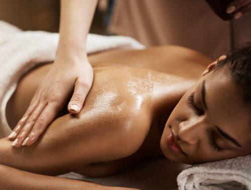 Close up photo of beautiful african girl enjoying massage in spa salon.
